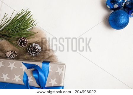 Festive background of Christmas presents. Wrapped gift box, ornament blue balls and strobila with fur and pine, top view with copy space in the middle. Congratulation and handmade decor concept