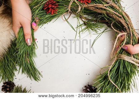 Process of making Christmas wreath by unrecognizable woman, top view. New Year holidays, festive decoration from pine and strobila, national traditions concept