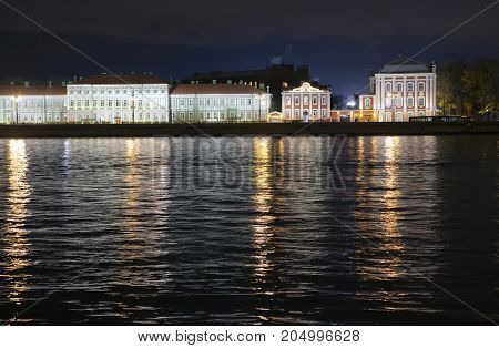 Night view of the University embankment of St. Petersburg through the Neva River