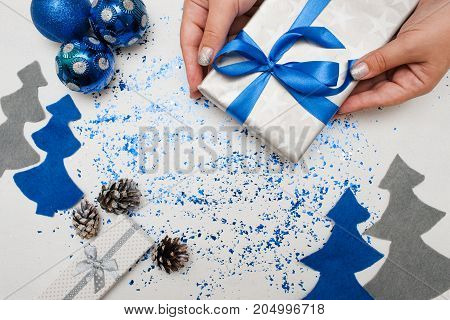 Preparing Christmas decor and gifts. Woman put on table wrapped present, ornament blue balls and felt fir tree nearby with spangles spread around, top view and copy space. Handmade decoration concept