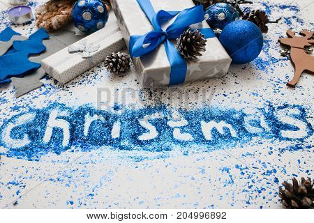 Christmas inscription. Decor and gifts backdrop. Close up wrapped presents and different handmade ornaments, bright spangles spread around. Festive background of holiday decoration concept