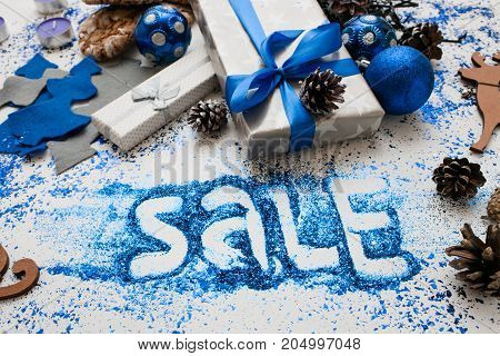 Big sale on Christmas and New Year holidays. Close up wrapped presents and different handmade ornaments with informative inscription beneath. Festive and colorful background concept