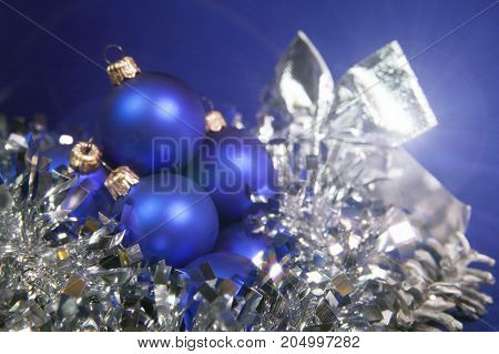 Blue New Year balls and tinsel on a blue background