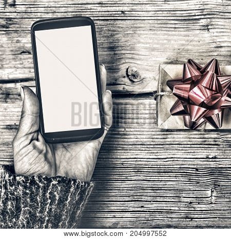 Closeup Of A Smartphone In The Hands Of A Woman And A Gift Box With A Red Bow On A Wooden Table.