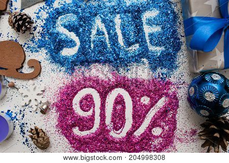Sales on Christmas and New Year holidays, top view close up. Colorful decoration with informative inscription of 90 pct discount for shop-windows, shopping malls and advertizing background concept