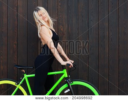 Beautiful blond girl in sexy outfits posing with a fixed bicycle on the background of their old wooden boards on the street. the wind blows her hair. Outdoor.