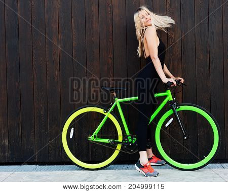The wind blows her hair. Beautiful blond girl in sexy outfits posing with a fixed bicycle on the background of their old wooden boards on the street. Outdoor.
