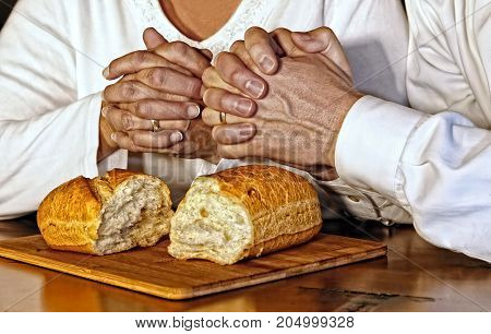 A husband and wife pray together giving thanks for the blessings of food and spiritual communion with God.