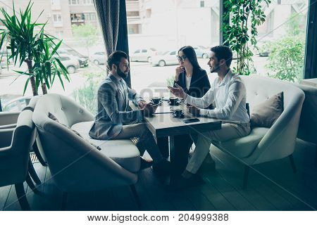 Young Business Partners Are Making A Deal With Lawyer About Their Business In A Fancy Restaurant`s T