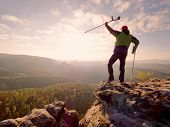 Hiker with hurts knee. Man with leg in join immobilizer stay on summit and raise medicine crutch above head. Hiker achieved mountain peak within surmount pain. poster