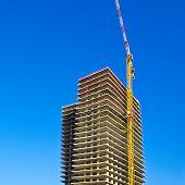 Crane and building under construction in Tel-Aviv. Industrial construction crane in Israel. poster