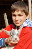 teenage boy portrait outdoors with little goat in hands poster