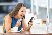 Excited on line buyer paying with credit card using a smart phone sitting in a bar terrace poster