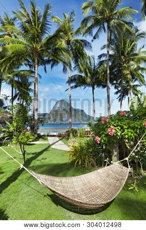 Tropical garden in front of the sea, hammock between a palm trees, El-Nido, Philippines