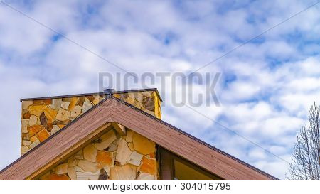 Panorama Frame Close Up Of The Roof Of A House Against Trees And Sky With Cottony Clouds
