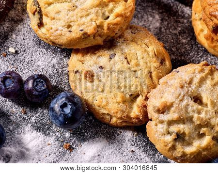 Serving food on slate onto wooden table. Oatmeal cookies biscuit with blueberry on picnic dark tiles countrylike. Chocolate Xmas holiday chip cookies tied with string. Chemical-free sweet foods.