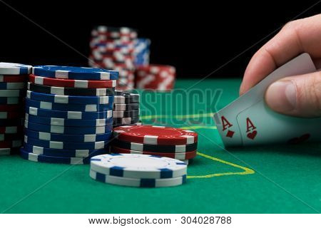 A Poker Player Looks At His Cards By Lifting Them On A Green Table Poker Chips Are In The Stack Next