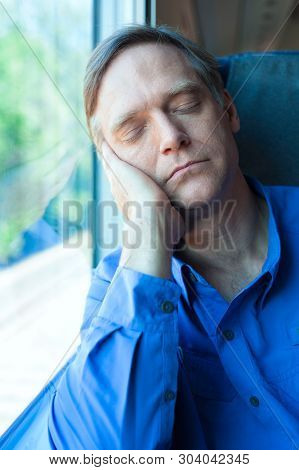 Caucasian Man Wearing Blue Shirt In Early Fifties Sleeping And Resting Against Train Window