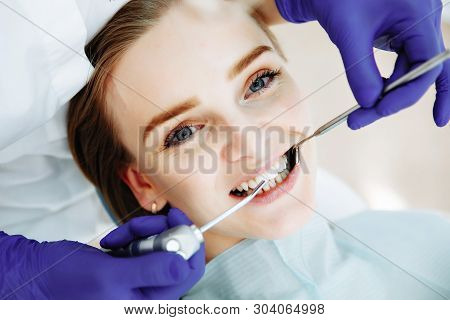 Woman At The Dentist Smiling. Work Of Stomatologist With Patient.