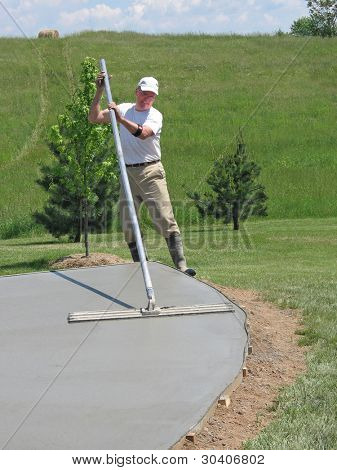 Worker smoothing a concrete slab with a bull float