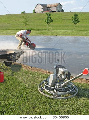 Worker cutting a groove in a concrete slab