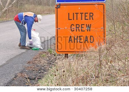 Volunteer collecting litter along country road