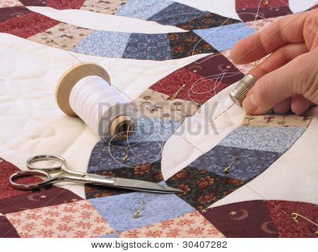 Hand-quilting of a double-wedding ring pattern quilt