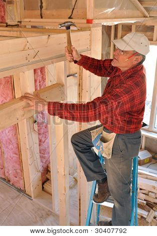 Carpenter pounding a nail into an interior partition
