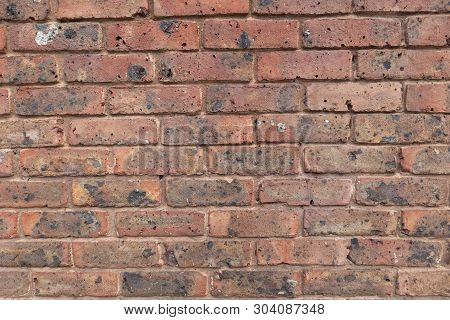 Red Brick Wall With Holes And Grime, Close-up Photo