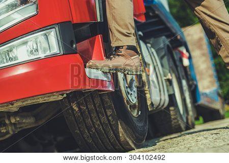Truck Driver And His Job Conceptual Photo Of Men Getting Into Semi Truck. Leg Closeup. Transportatio