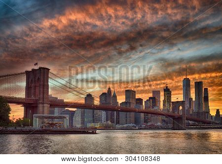 Silhouette Of Manhattan Skyline With Brooklyn Bridge At Sunset - Hdr Image.
