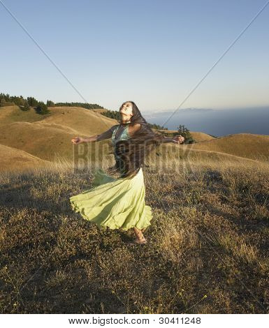 Passionate woman dancing on hillside