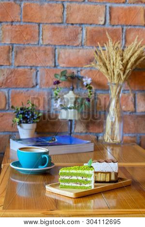 Chocolate Cake And Matcha Green Tea Sponge Cake  On Wooden Table With A Coffee Cup
