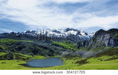 Lago De La Ercina In Valley Against Snowy Peaks Of Cantabrian Mountains Outdoors. Covadonga, Spain