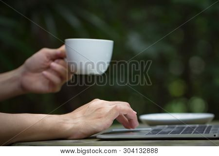 Young Business Woman Hands Typing On Laptop Computer Keyboard And Holding Coffee Or Tea Cup. Female