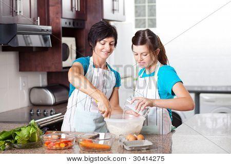 teen daughter helping mother baking in kitchen