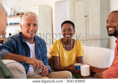 Group of multiethnic friends talking and drinking tea at home. Mature and senior couple chatting together while sitting on couch. Happy man and smiling woman in conversation at home and drinking coffe