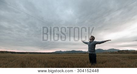 Young Man Standing In Autumn Meadow Under Cloudy Evening Sky With His Arms Wide Open.