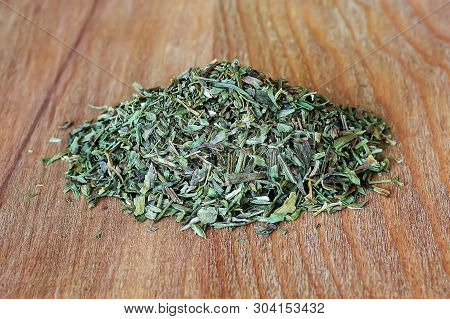 Heap Of Dry Tarragon Or Estragon Flakes On A Brown Wooden Cutting Board. Natural Food Spices And Sea