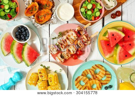 Summer Bbq Or Picnic Food Concept. Selection Of Fruits, Salad, Grilled Meat And Potatoes. Top View T