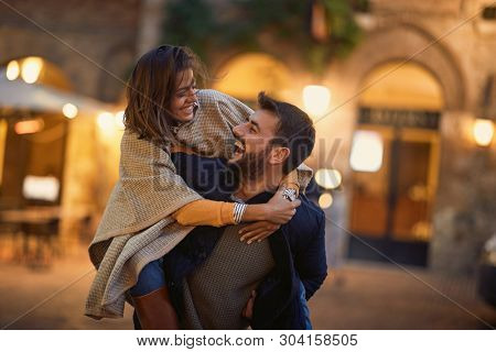 Smiling man and woman in love, enjoying in evening walk together