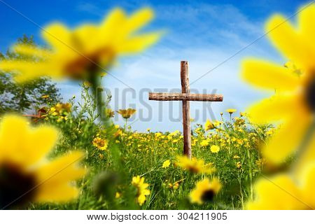 close up wooden cross on flower covered landscape over sunny blue sky