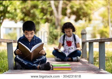 Asian Children Are Relaxing Reading In The Garden.education And People Concept.back To School