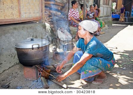 LOMBOK, INDONESIA-FEBRUARY 14: Woman makes Indonesian food on traditional way on February 14, 2012 in Sade village, Lombok, Indonesia.They always cooking food in open fire in front of the house