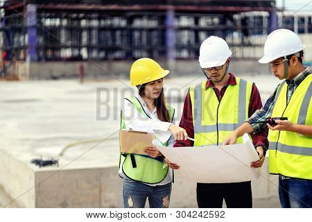 Foreman 3 People Are Held A Blueprint To Discuss The Construction Structure.woman Engineers Wear Saf