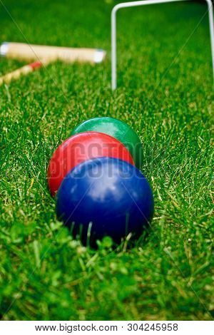 Three Colorful Croquet Balls Lined Up With Wicket In Background