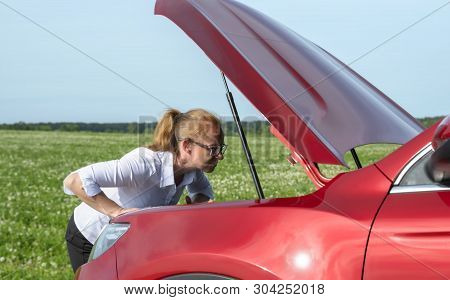 Woman Expresses Bewilderment When She Looks Under Hood Of Car.