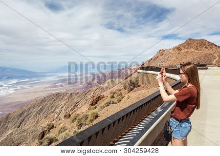 Young Beautiful Woman Take A Picture Of Badwater Basin From Dante's View Terrace In Death Valley Nat