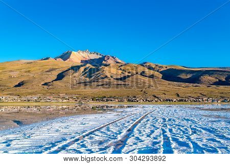 View Of The Dormant Volcano Tunupa And The Village Of Coqueza At The Uyuni Salt Flat In Bolivia