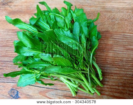 Raw Green Living Cress Or Watercress Leaves Bunch On Wooden Table Background. Organic Healthy Leaves